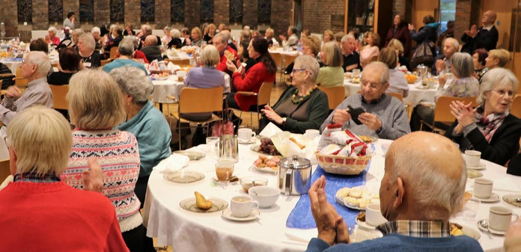 Full hall of U3A members sitting round tables laden with cakes and other food