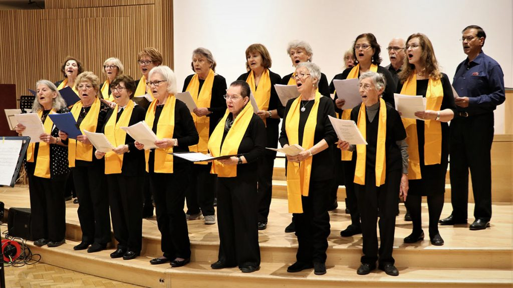 Choir with ladies wearing matching orange scarfs