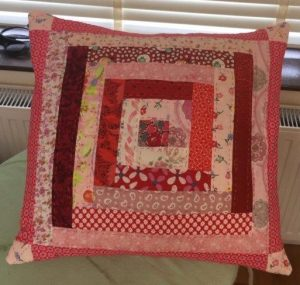 Patchwork cushion in various shades of red