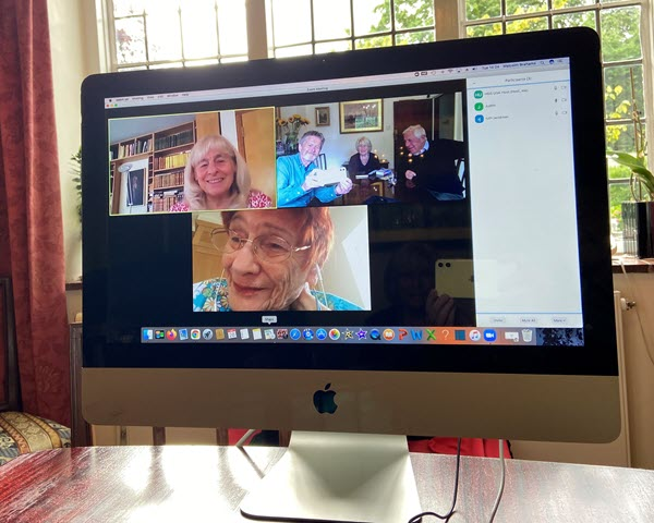 Computer screen showing members meeting online and in a private home
